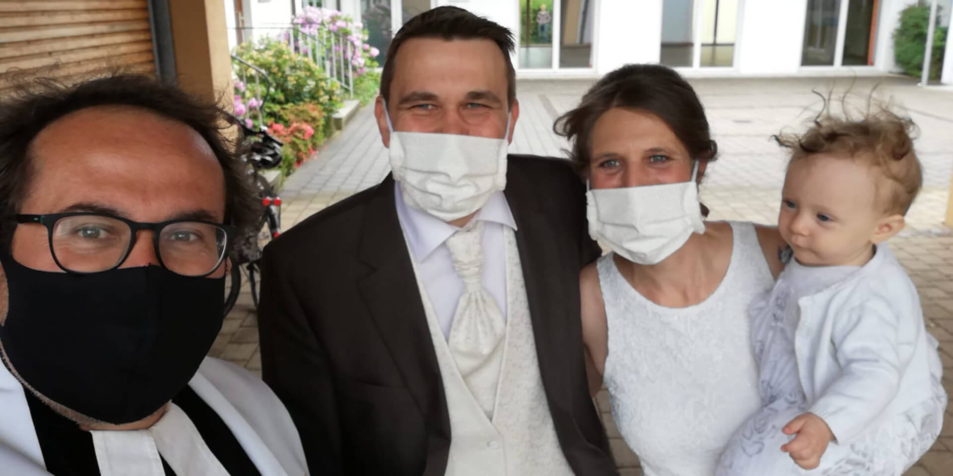 Eine junge Familie und ein Pfarrer tragen Masken auf einem Selfie nach einer Taufe